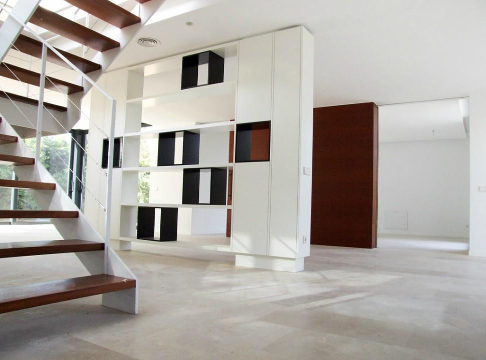 Salón con escalera doble altura. Vivienda Unifamiliar en Monteclaro, Pozuelo de Alarcón, Madrid.Un proyecto del estudio de arquitectura FH2L Arquitectos.