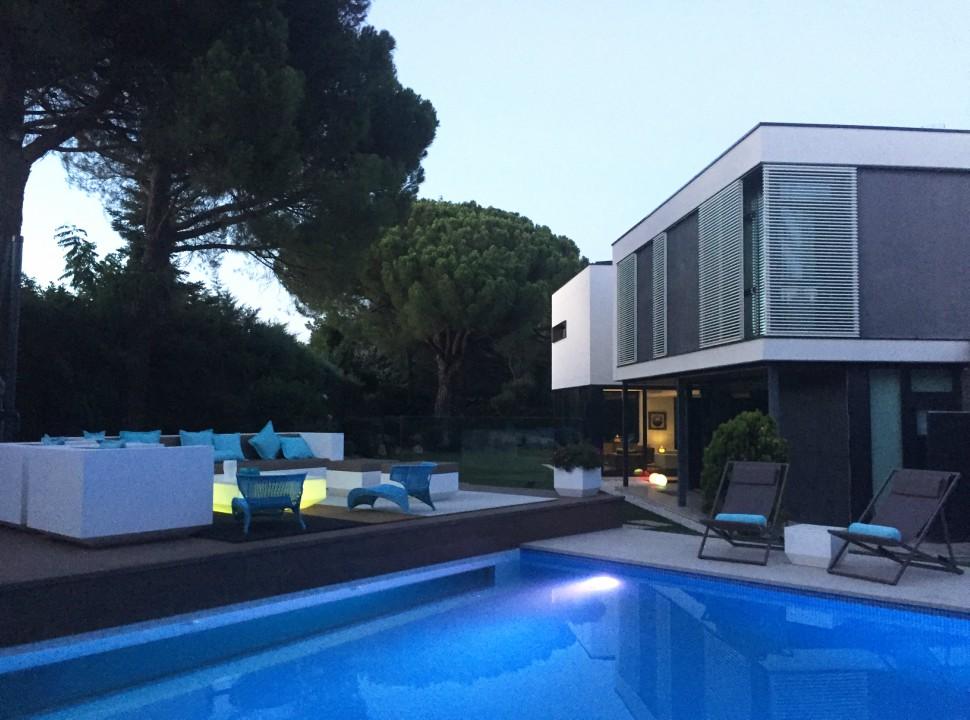 Vista exterior, jardín y piscina, zona chill out. Vivienda Unifamiliar en Monteclaro, Pozuelo de Alarcón, Madrid. Un proyecto del estudio de arquitectura FH2L Arquitectos.