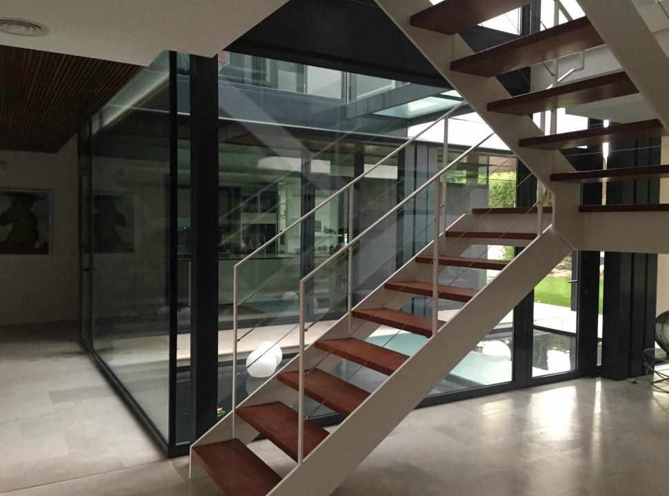 Escalera doble altura. Vivienda Unifamiliar en Monteclaro, Pozuelo de Alarcón, Madrid.Un proyecto del estudio de arquitectura FH2L Arquitectos.